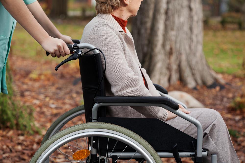 Disabled elder woman on wheelchair with nurse