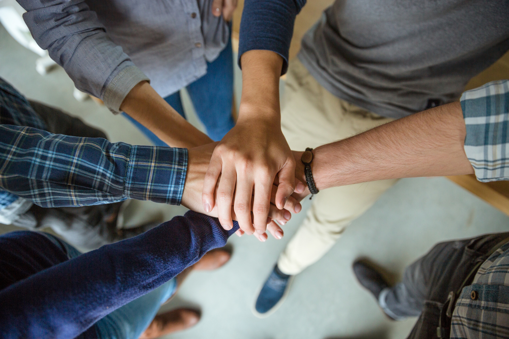 Top view of people joining hands together as a symbol of partnership-1